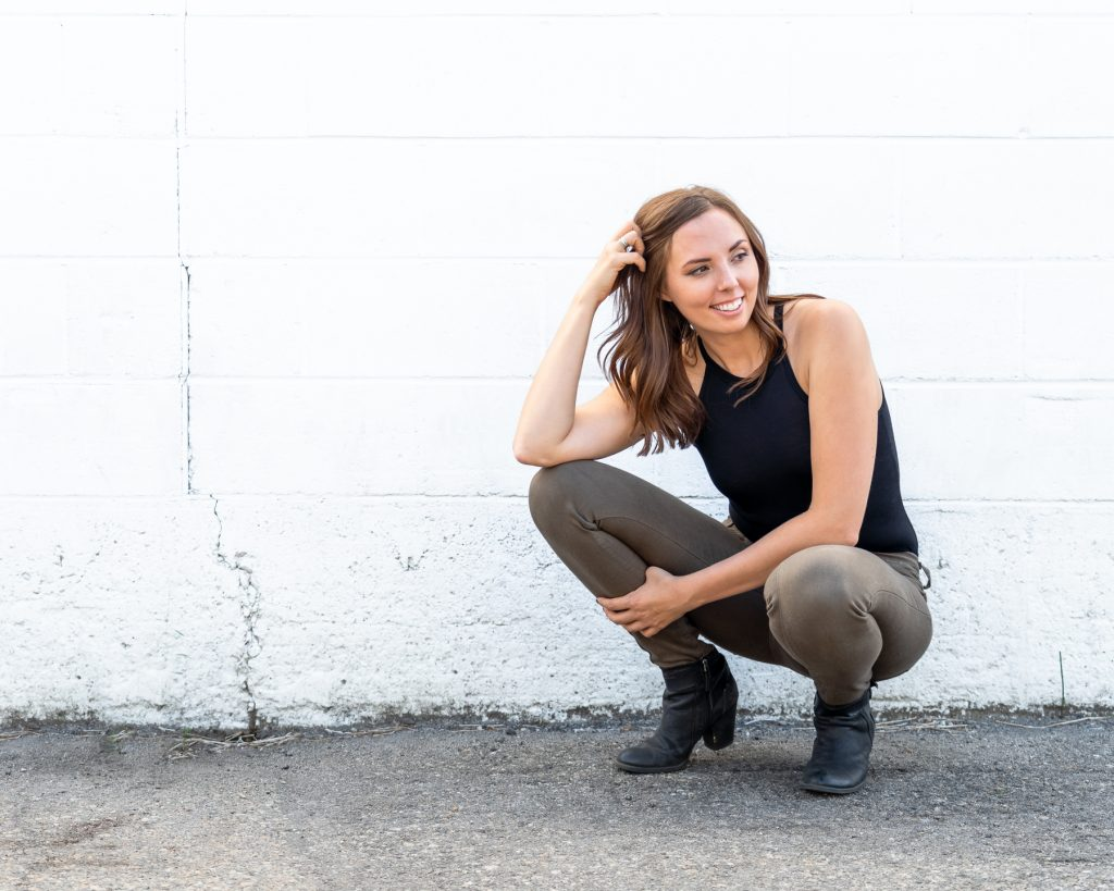 photo of woman squatting down in front of white wall