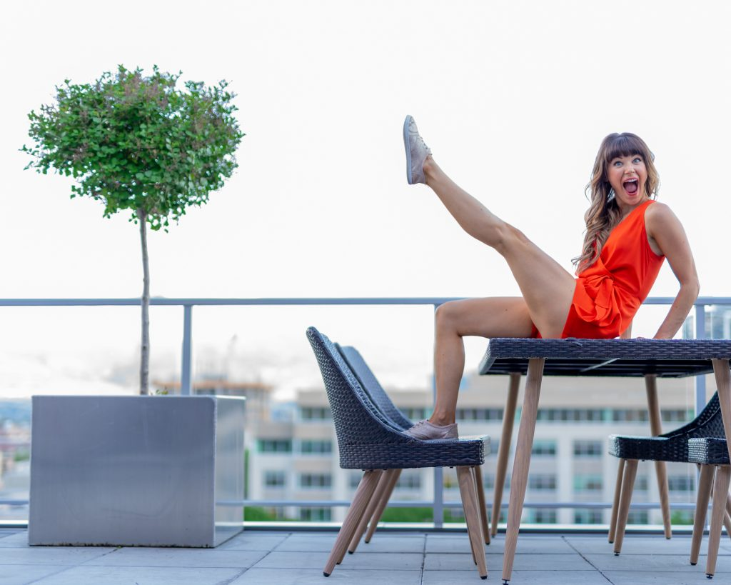 young woman sitting on table kicking leg in air personal brand photo