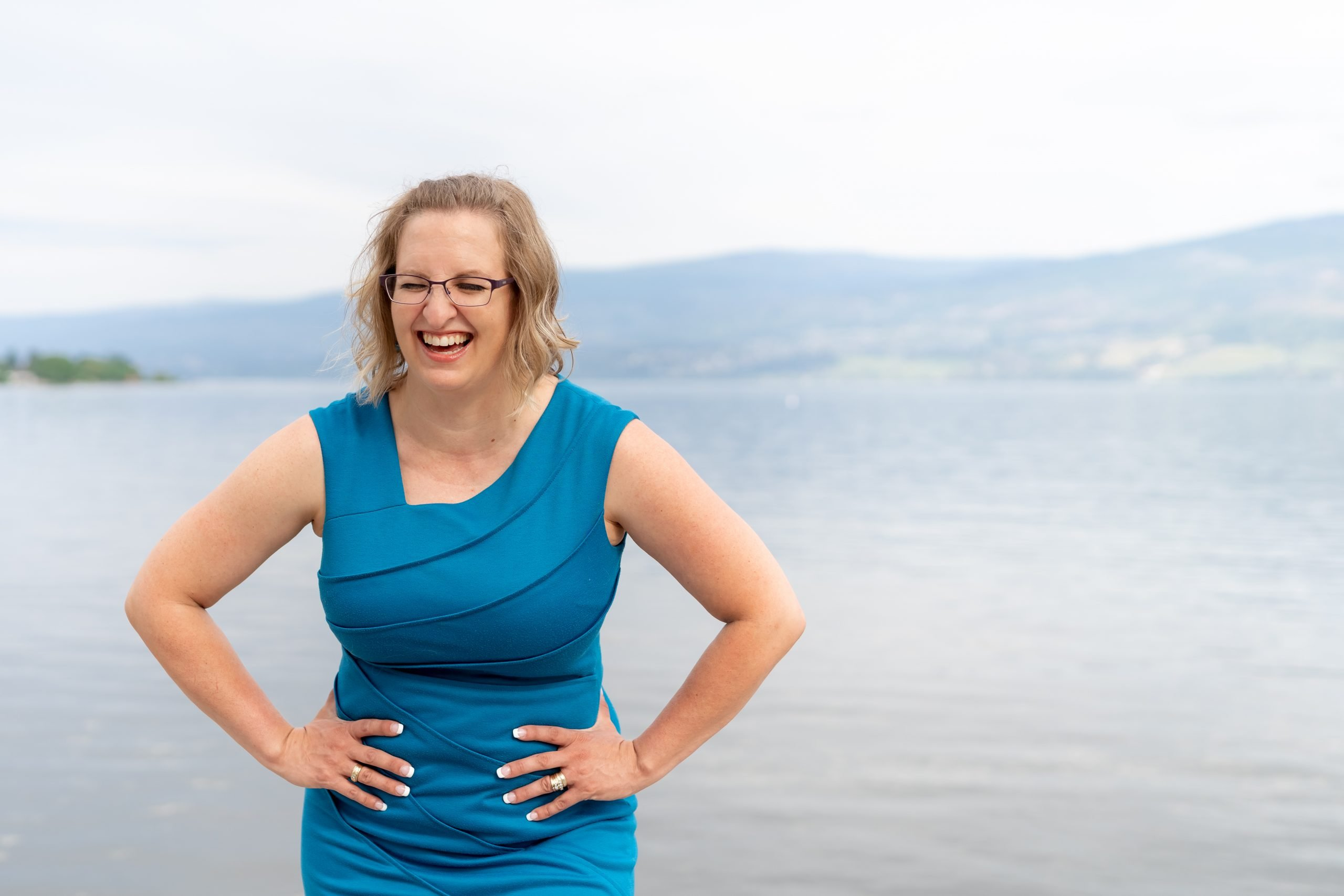 woman wearing blue dress and laughing for brand photos