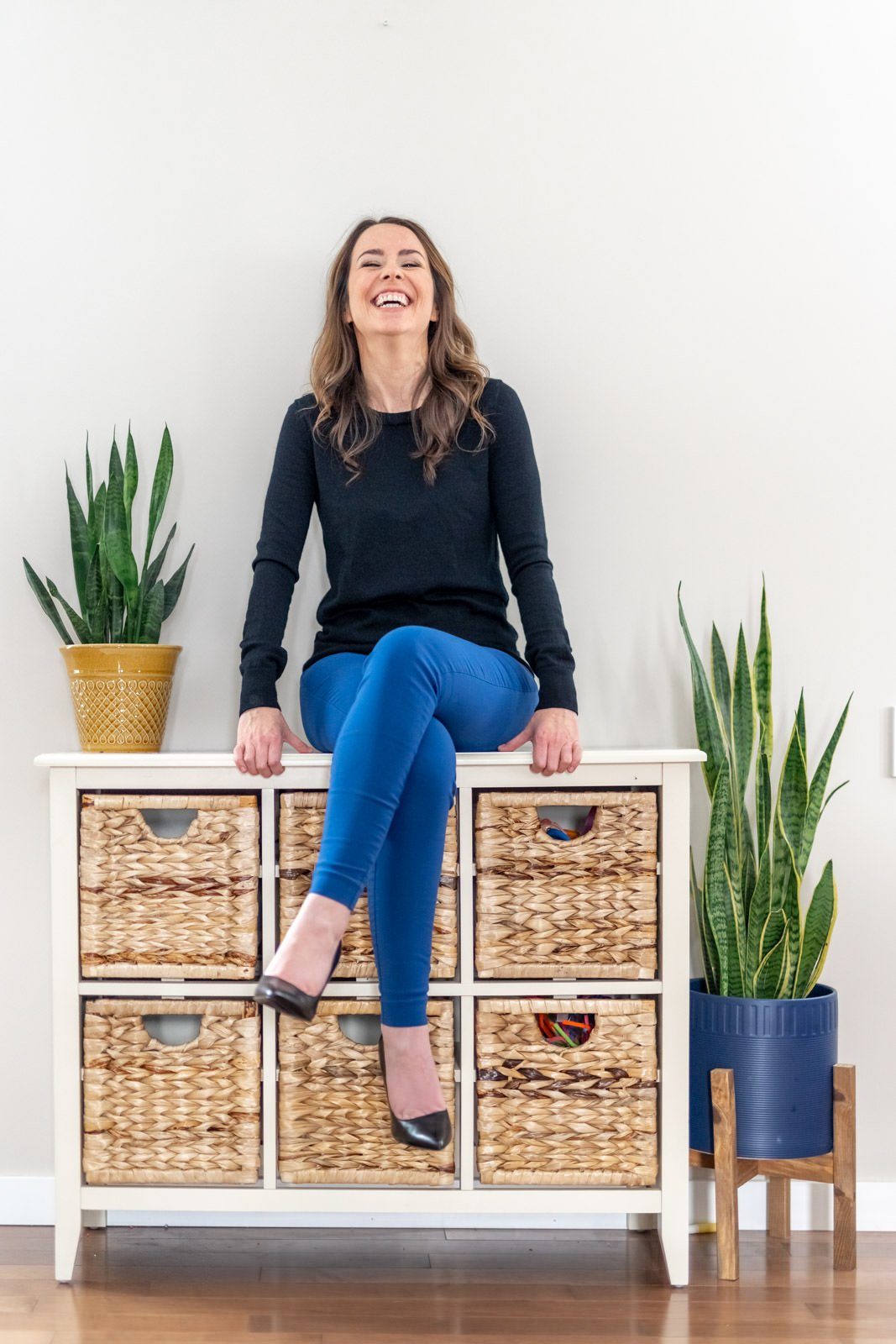 woman sitting on dresser laughing for personal branding photoshoot