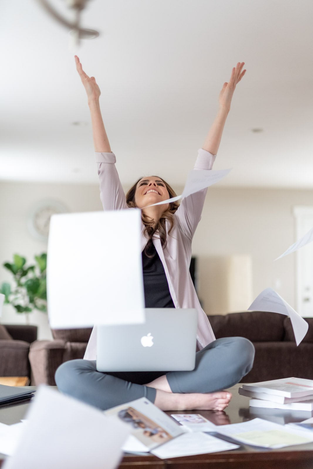 woman sitting on table throwing papers in the air for personal branding photoshoot