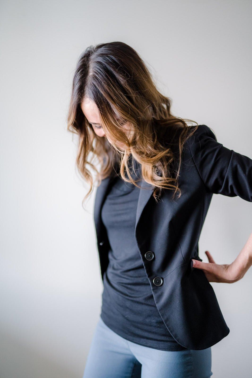 woman in black blazer looking down business portrait