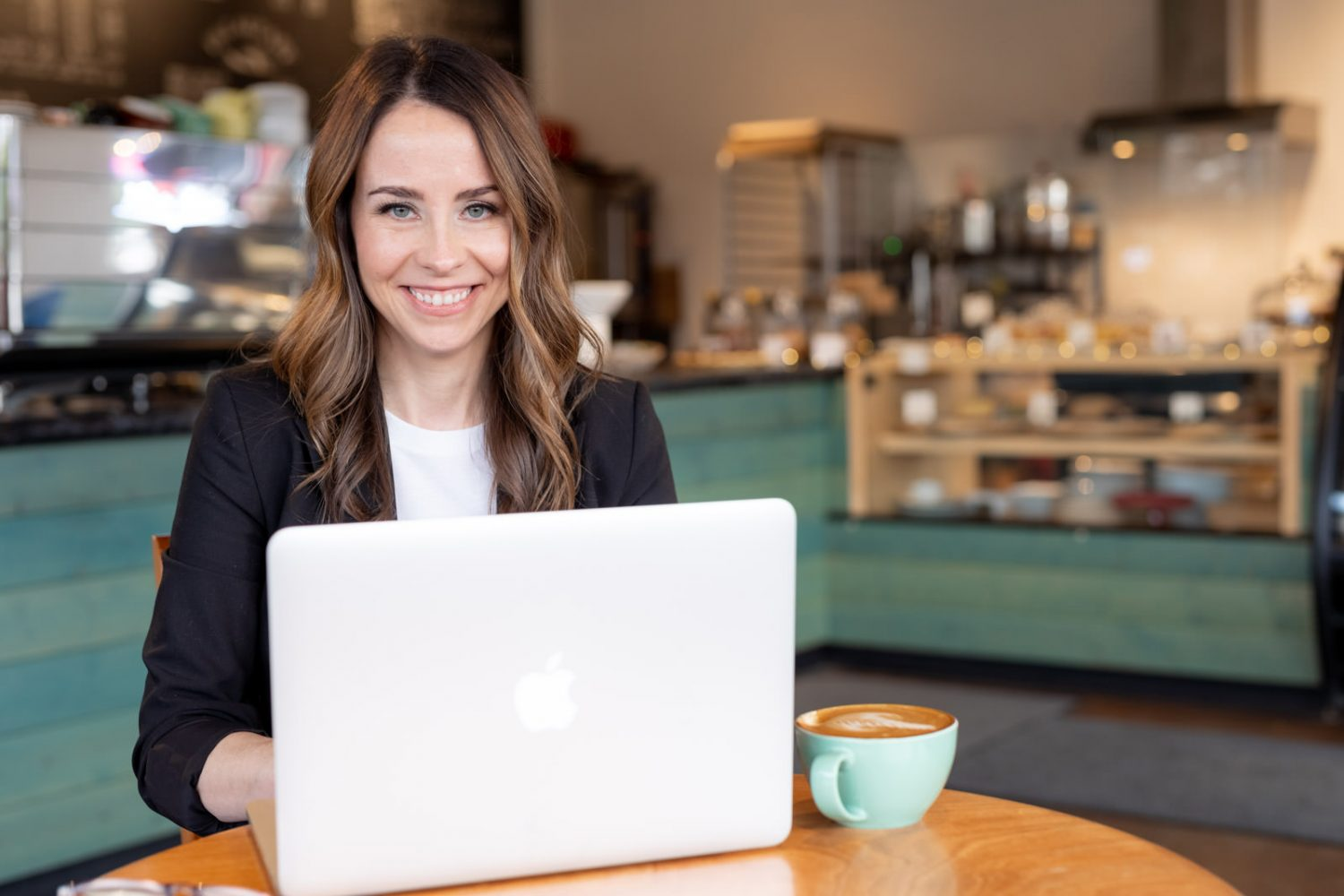 woman working on laptop in coffee shop smiling at camera personal branding photo