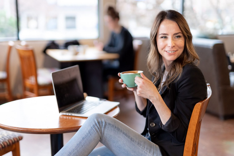 woman holding green mug in coffee shop environmental branding photos