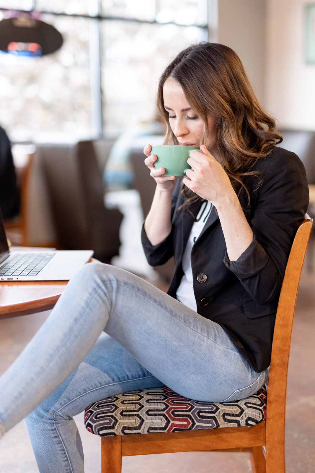 woman in coffee shop sipping from green mug branding photography
