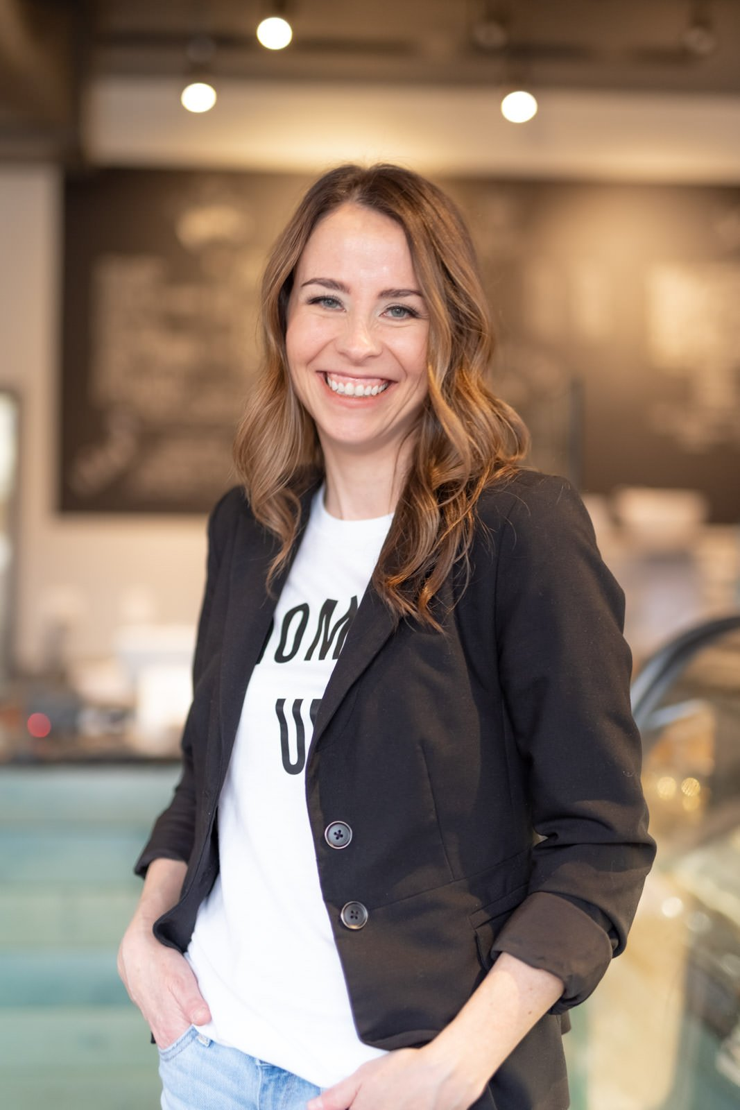 woman standing in coffee shop smiling for personal branding photoshoot
