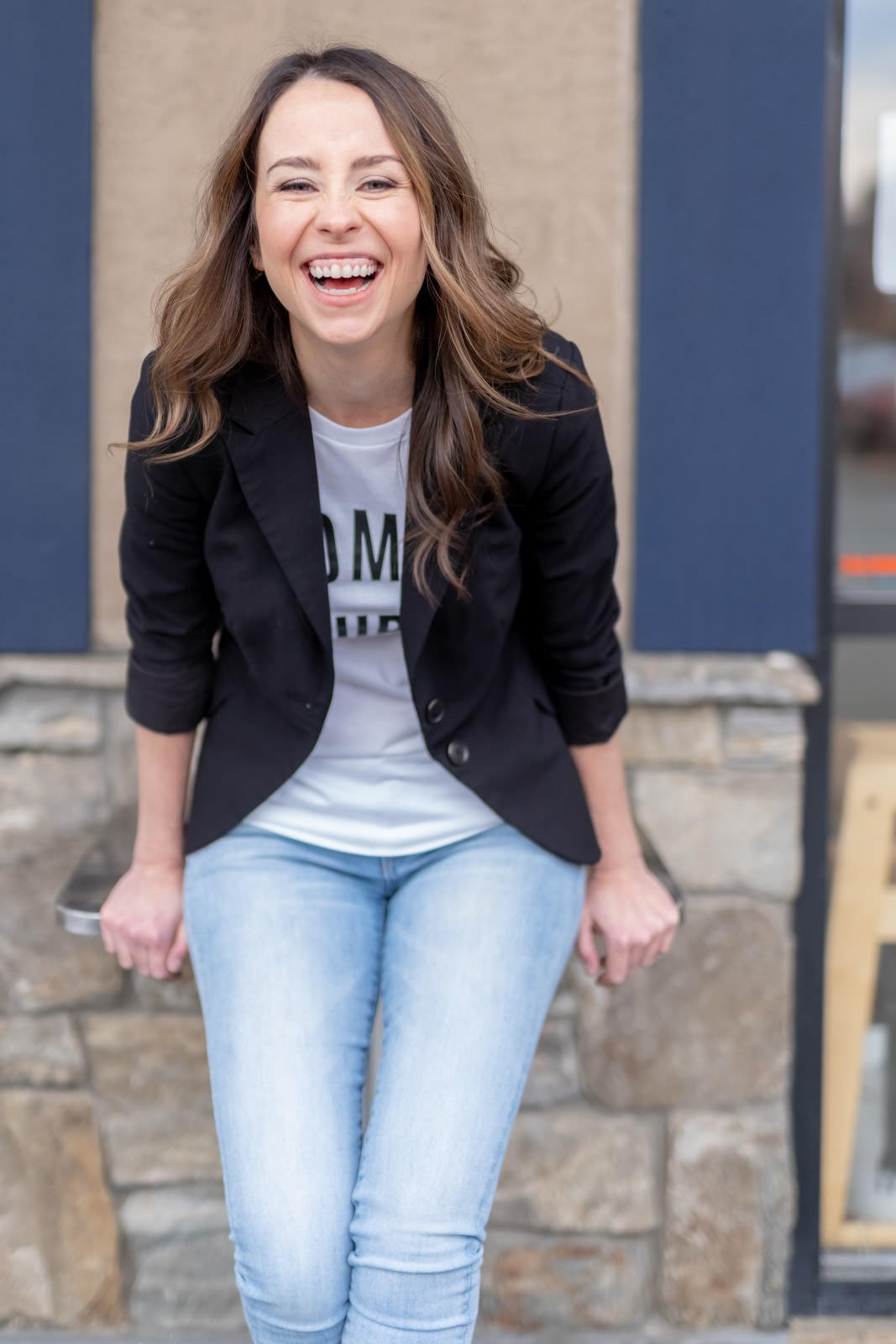 woman leaning forward laughing for personal branding photoshoot